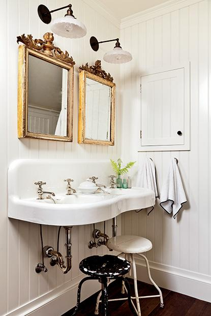 -From Garden & Gun. French mirrors add elegance to a rustic bathroom; anchored by an antique double sink and accented by a personal touch. The white stool is from the doctor's office of designer Barbara Westbrook's grandfather.