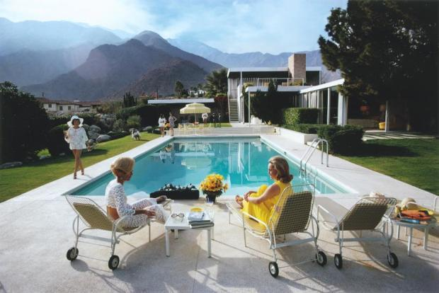 """""""Poolside Gossip"""" was taken in 1970 by Slim Aarons. It sets the tone for the glamour of the decade."""